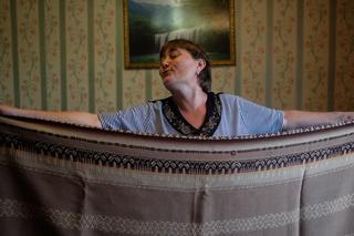 Olga shows off a blanket that was made in Estonia from Siberian wool. Her mother was deported to Siberia in 1949, but did not return with her family to their homeland in 1957, because she had two little daughters by that time. They kept ties.